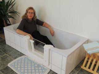Frau sitzt in Badewanne mit Tür